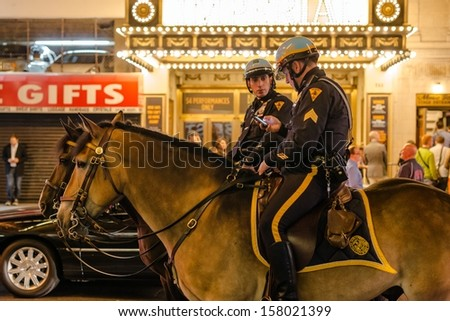 NEW YORK, USA - SEPTEMBER 28, 2013: Police officers ride their horses on Broadway near Times Square at night on September 28, 2013 in Manhattan, New York City, USA. - stock photo