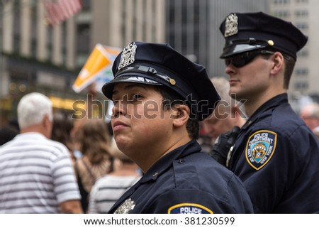 New York, USA - 21 September 2014:  Police officers watch people marching and campaigning for greater environmental awareness during the Peoples Climate March through New York City - stock photo