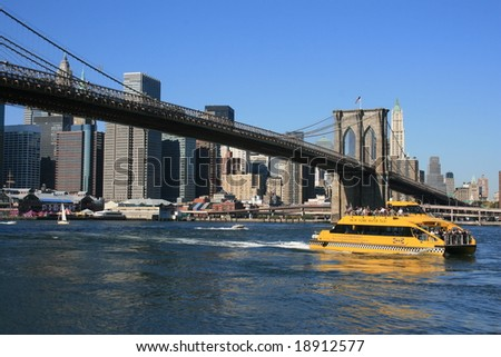 New York - Water Taxi passing under the  Brooklyn Bridge along the East River, October 2008, New York  City. - stock photo