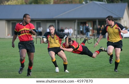New Zealand club Rugby action, Burnham v Kirwee 6 May '06.  Kirwee fullback Simon Murdoch breaks the tackle of his Burnham counterpart Matthew Addsworthy. - stock photo