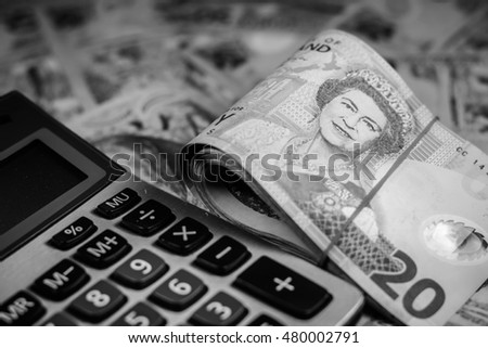 New zealand dollar and calculator ready for business and for summer school education isolated on white background,Focus on eye of a woman on banknote with black and white color