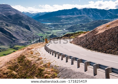 New Zealand Highway:  A scenic road passes through mountains and valleys north of Queenstown on New Zealand's South Island.  - stock photo