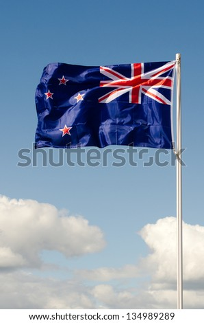 New Zealand National flag wave above long white clouds.
