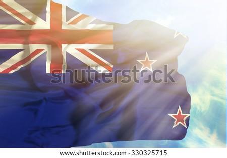 New Zealand waving flag against blue sky with sunrays - stock photo