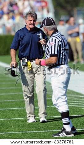 NEWARK, DE - OCTOBER 9: University of Maine football head coach Jack Cosgrove (facing) discusses a call with a referee in a game October 9, 2010 in Newark, DE - stock photo