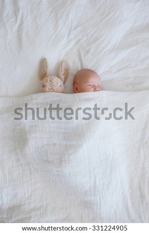 Newborn and plush rabbit tucked into a cozy white bed - stock photo