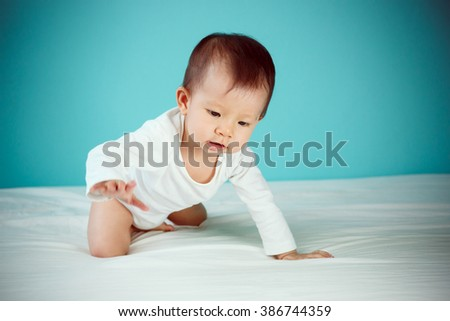Newborn are crawling on white bed (soft focus on the eyes)