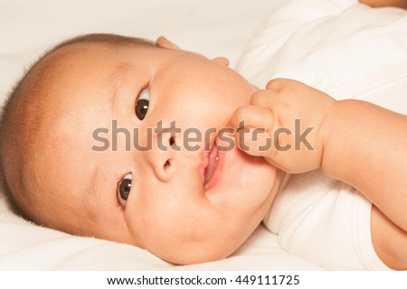 Newborn Asian baby girl lying and happiness on a bed. - stock photo