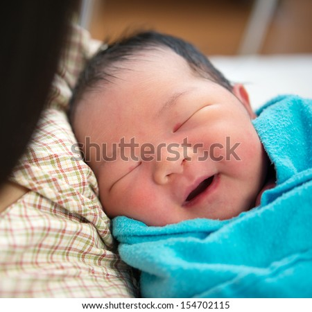 Newborn Asian baby girl smiling and fall asleep in mother's arms, inside hospital room - stock photo