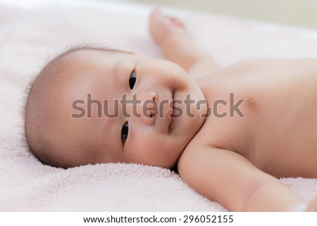 Newborn Asian baby lying down on bed happy. - stock photo