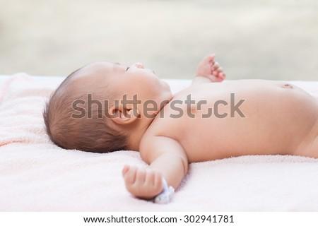 Newborn Asian baby sleep on bed happy. - stock photo