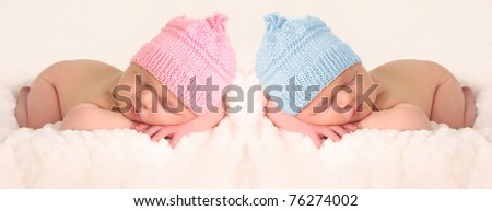 Newborn babies in pink and blue knitted hats. - stock photo