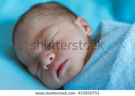 Newborn baby a sleeping covered with blue cloth at the hospital