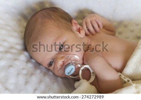 Newborn baby awake and quiet with his pacifier, on a white blanket. - stock photo