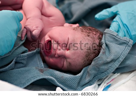 Newborn baby being cleaned up after birth