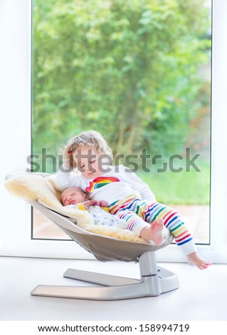Newborn baby boy and his toddler sister relaxing in a swing next to a big window and door to the garden - stock photo