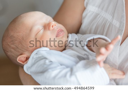 Newborn baby boy asleep in mother's arms