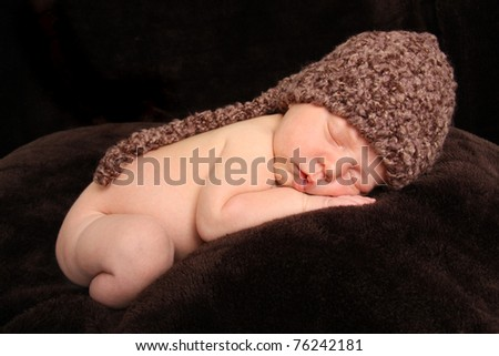 Newborn baby boy asleep wearing a knit hat. - stock photo