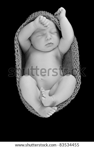 Newborn baby boy asleep wrapped in a knitted cocoon. - stock photo
