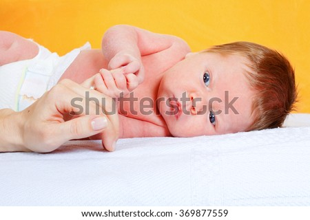 Newborn baby boy holding his mother's finger - stock photo