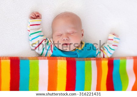 Newborn baby boy in bed. New born child sleeping under a colorful blanket. Children sleep. Bedding for kids. Infant napping in bed. Healthy little kid shortly after birth. Clothing for kids. - stock photo
