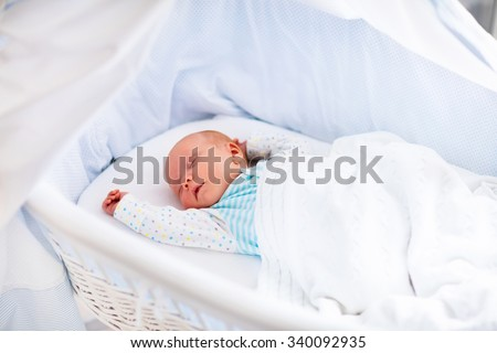 Newborn baby boy in bed. New born child sleeping under a white knitted blanket. Children sleep. Bedding for kids. Infant napping in bed. Healthy little kid shortly after birth. Cable knit textile. - stock photo