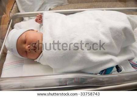 Newborn baby boy in hospital bassinet - stock photo