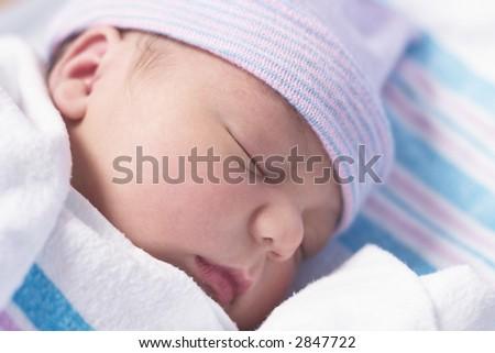 Newborn baby boy in hospital nursery resting peacefully - stock photo