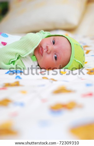 Newborn baby boy lying on a colorful blanket, and looking at camera. - stock photo