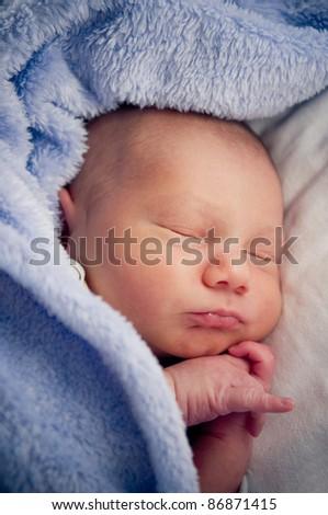 Newborn baby boy lying under blue blanket - stock photo