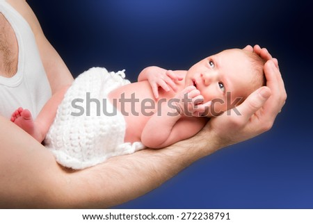 Newborn baby boy on the father's hand. - stock photo