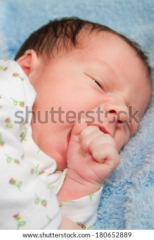 Newborn baby boy portrait while learning to suck on his fist - stock photo