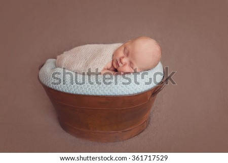 Newborn baby boy posing in  vintage metal tude