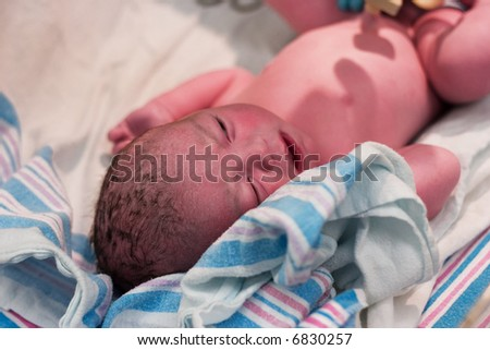 Newborn baby boy resting after being examined in delivery room - stock photo