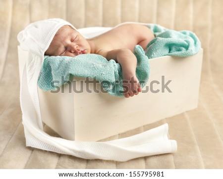 Newborn baby boy sleeping in a wooden case - stock photo