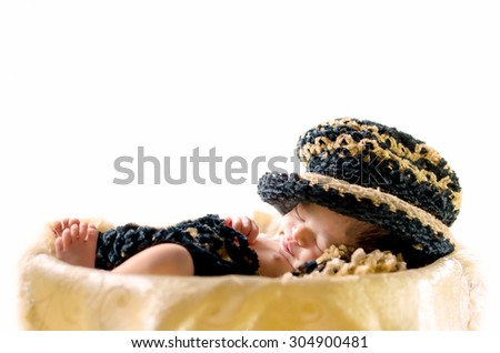 Newborn baby boy sleeping in basket wearing black & brown hat and blanket isolated in white background - stock photo