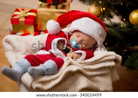 Newborn baby boy sleeping in living room at Christmas tree and boxes with presents - stock photo
