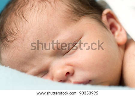 Newborn Baby boy sleeping on a blue blanket. - stock photo