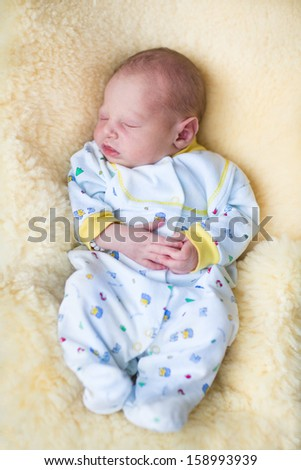 Newborn baby boy sleeping on a sheepskin - stock photo