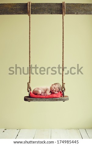Newborn baby boy sleeping on an antique swing - stock photo