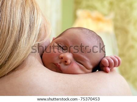 Newborn baby boy sleeping on mother's shoulder - stock photo
