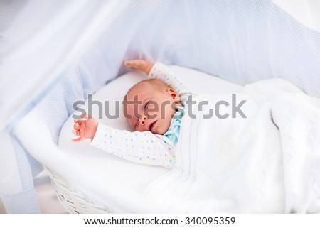 Newborn baby boy waking up on a sunny morning in white bed. New born child sleeping and stretching in moses basket under knitted blanket. Children sleep. Bedding for kids. Infant napping in bed.  - stock photo