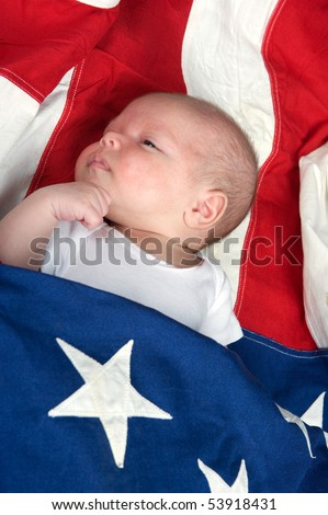 Newborn baby boy wrapped in the American flag - stock photo