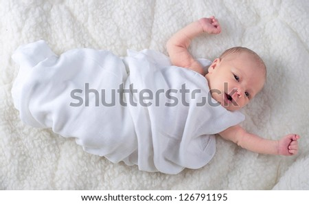 Newborn baby boy wrapped in white blanket - stock photo
