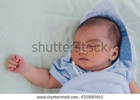 newborn baby concept : close up newborn cute Asian baby boy sleeping with blue blanket with space for text : people concept - stock photo