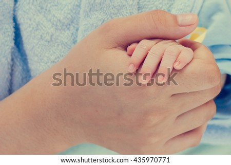 Newborn baby concept : newborn baby hand with mother hand in vintage tone style: mother day and people concept - stock photo