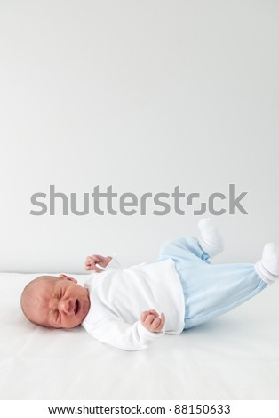Newborn baby crying on simple background - stock photo