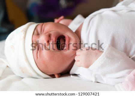 Newborn baby crying on the bed, selective focus - stock photo