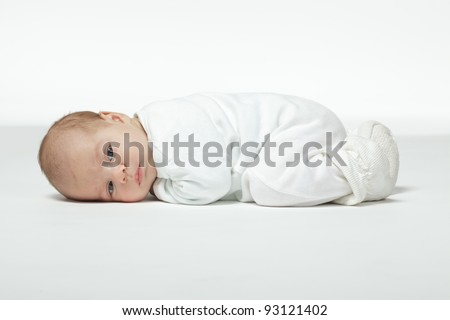 Newborn baby curled up lying on his stomach - stock photo