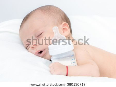newborn baby curled up sleeping on a blanket with feeding bottle - stock photo